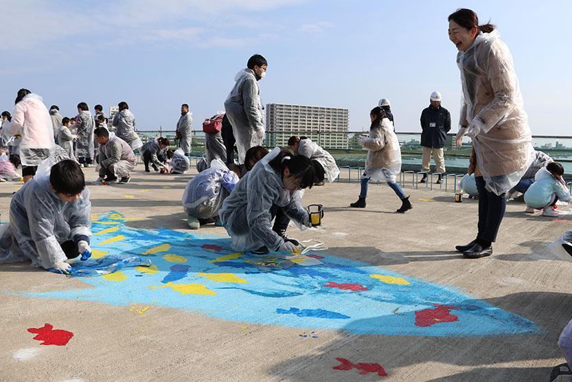 子どもたちが3色のペンキとスポンジで7種の魚を描いた