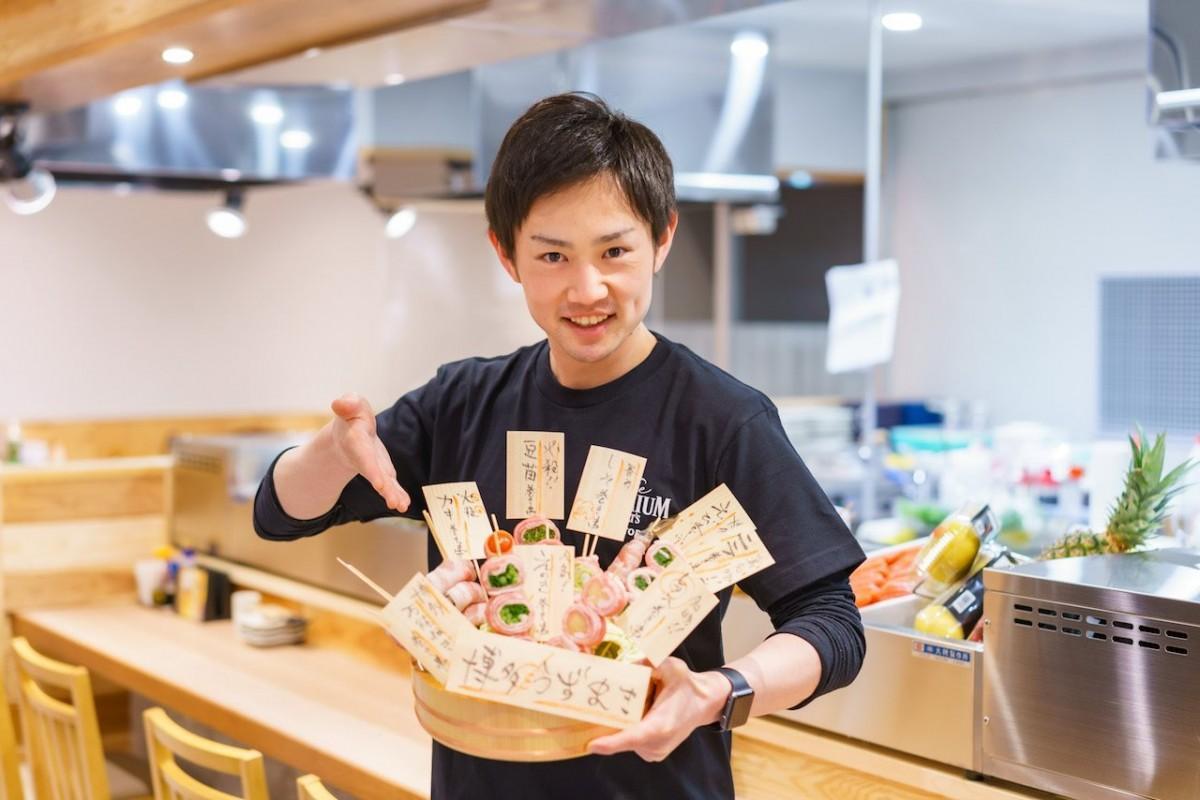炭火野菜巻き串を紹介する店長の石飛慶也さん