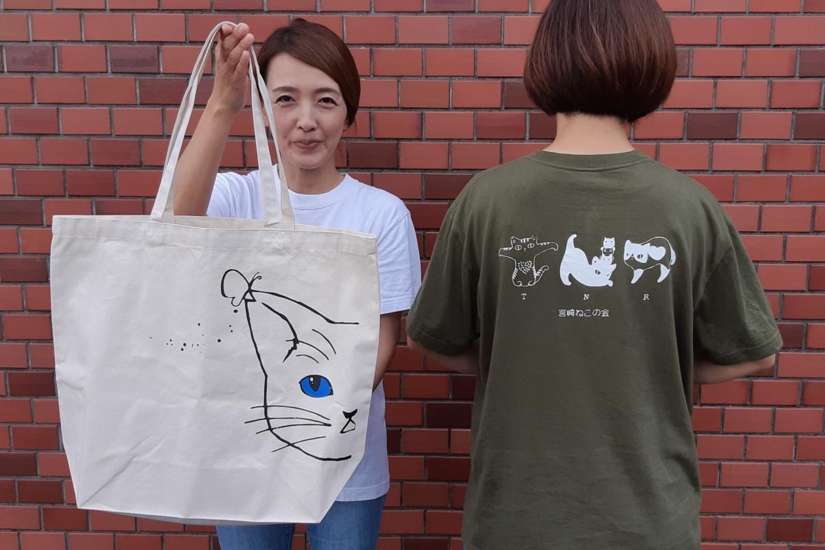 トートバッグを持つ会員の松下美紀さん。ねこの会オリジナルのTシャツは、今後イベント時に限定カラーなども販売する予定