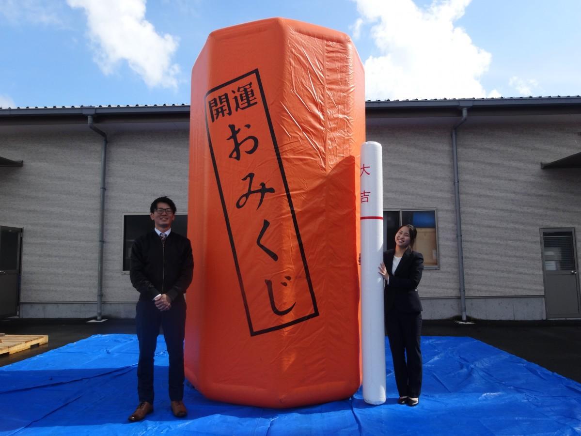 巨大おみくじを前に(左から )社員の日髙裕次郎さんと後藤由衣さん