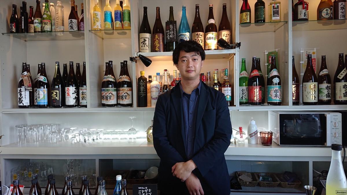 日南・串間の焼酎が並ぶ店内と江本さん