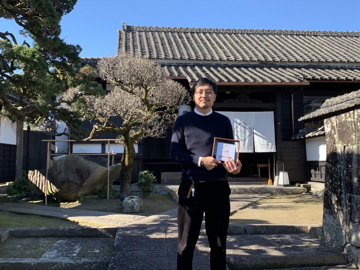 受賞した温泉宿 小鹿倉邸の前で賞を手にする、PAAK designの鬼束準三さん