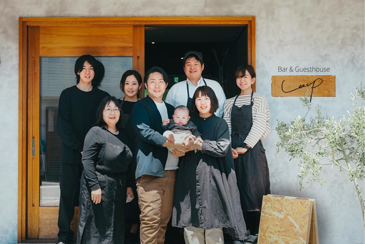 昨年10月に生まれた長男の芙來(ふき)くんを抱く上岡夫妻(前列中央)と、店舗スタッフ