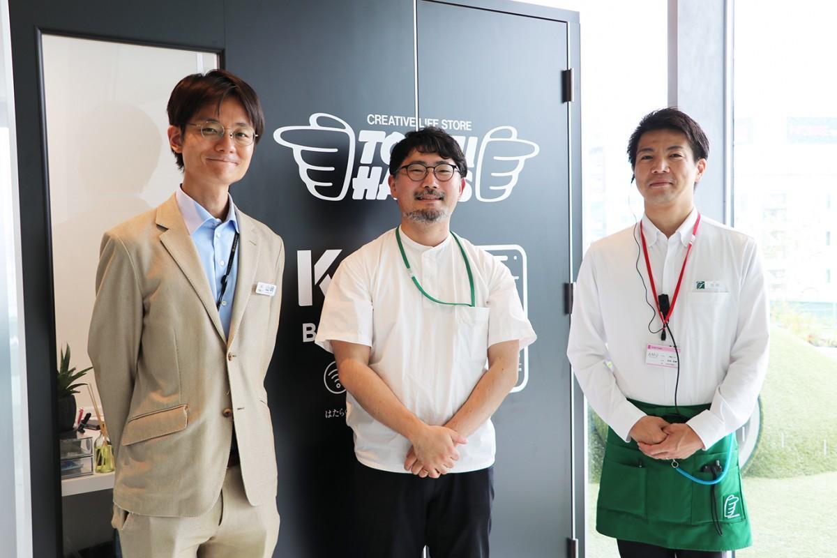 (画像左から)「KIW BRUNCH02」の前に立つ「JR宮崎シティ」の山崎雄大さん、「九州アイランドワーク」の馬渡侑佑さん、「東急ハンズ宮崎店」の宮田和典さん