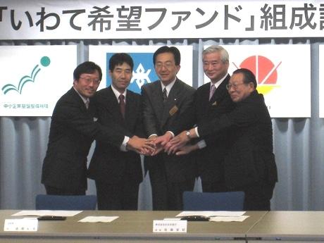 1月9日に行われた「いわて希望ファンド」の調印式の様子。出資する岩手県の達増拓也知事と北日本銀行の佐藤安紀頭取らが握手を交わした
