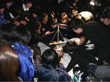 舞錐式の発火法で火おこしをする厨川中学校の男子生徒たち。回りには様子をうかがう人で人だかりができた
