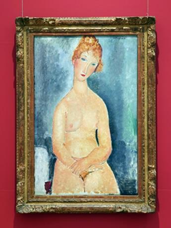 なで肩で瞳のない作風は、ひと目でモディリアーニとわかる作品。写真は「手を組んで坐る裸婦」、ホノルル美術館蔵