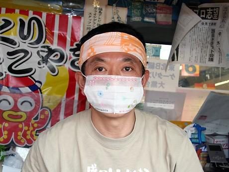 店頭で「マスク犬」シールを無料配布しながらマスクの大切さを訴える村井さん