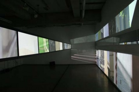 狭い空間に12枚のスクリーンを横に並べたさいとうさんのビデオインスタレーション。写真右に漏れた画像も作品の一部として表現する