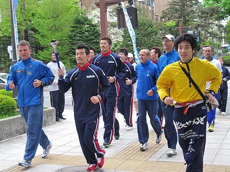 トーチを持って盛岡の街を走る岩手ビッグブルズ選手と各国のランナー