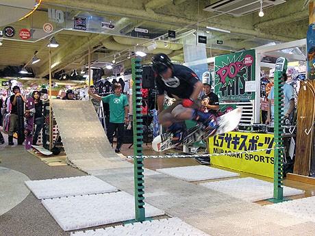 スノーボードの板の反発を使ってバーを飛び越える
