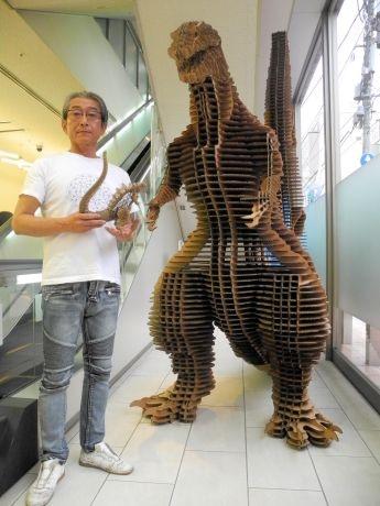 大迫力のゴジラと並ぶ松岡社長。手にはミニチュアサイズのゴジラも