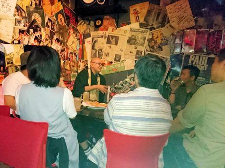 第1回目の様子。来店客に囲まれて話す佐々木さん(中央)