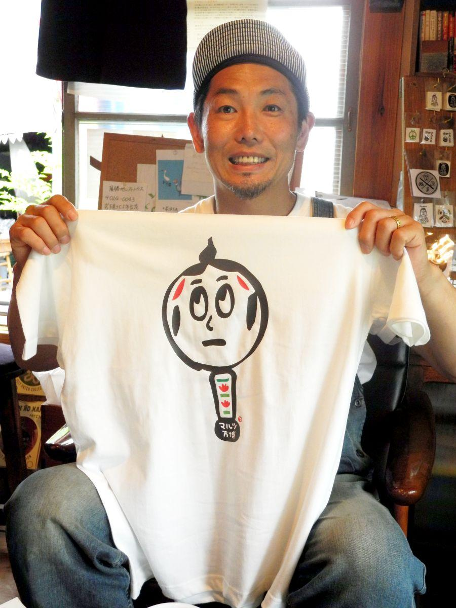 こけしTシャツを手に「ぜひ遊びに来て」と呼び掛ける吉田さん