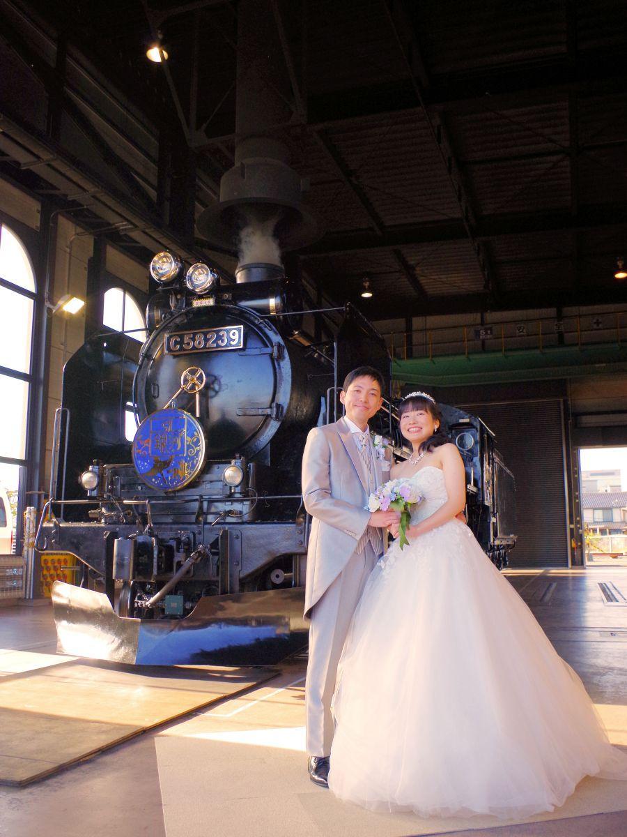 思い出の「SL銀河」の前で撮影を楽しむ新郎・祐太さんと新婦・加奈絵さん