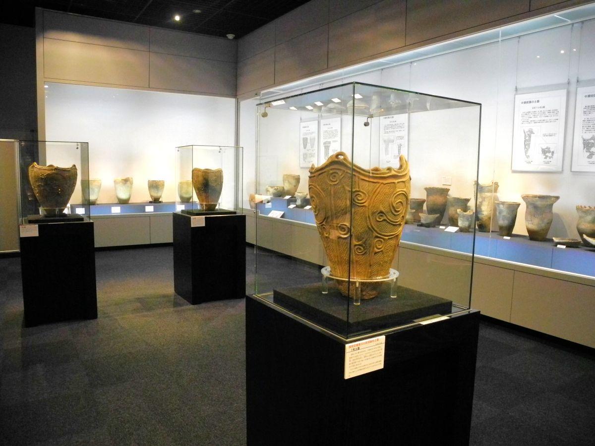 渦巻文が特徴的な「一号土器」(手前)をはじめ、「深鉢形土器」7個が並ぶ展示室