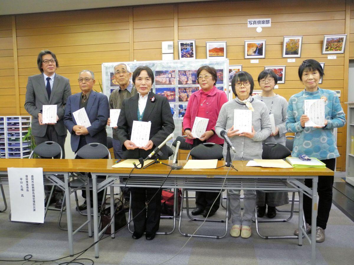 完成した手記集を手にする執筆者の皆さんと講師の斎藤さん