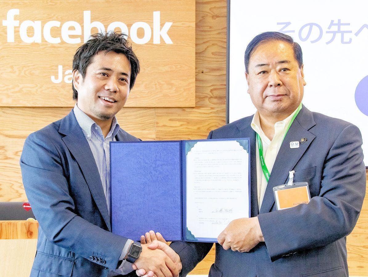 締結式で握手を交わす長谷川社長(左)と谷藤市長(右)