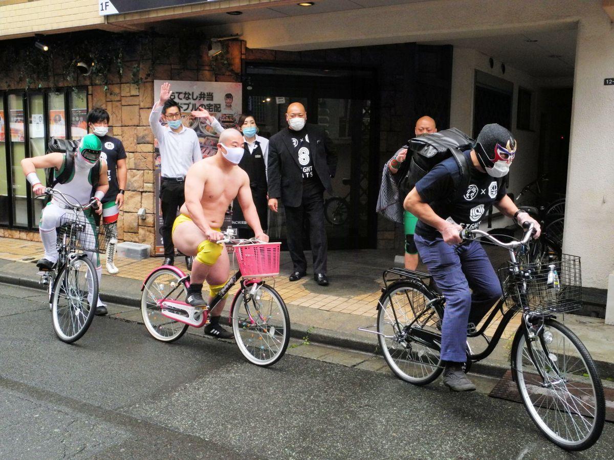 自転車に乗り、配達へ出発するレスラーの皆さん。先頭はザ・グレート・サスケさん