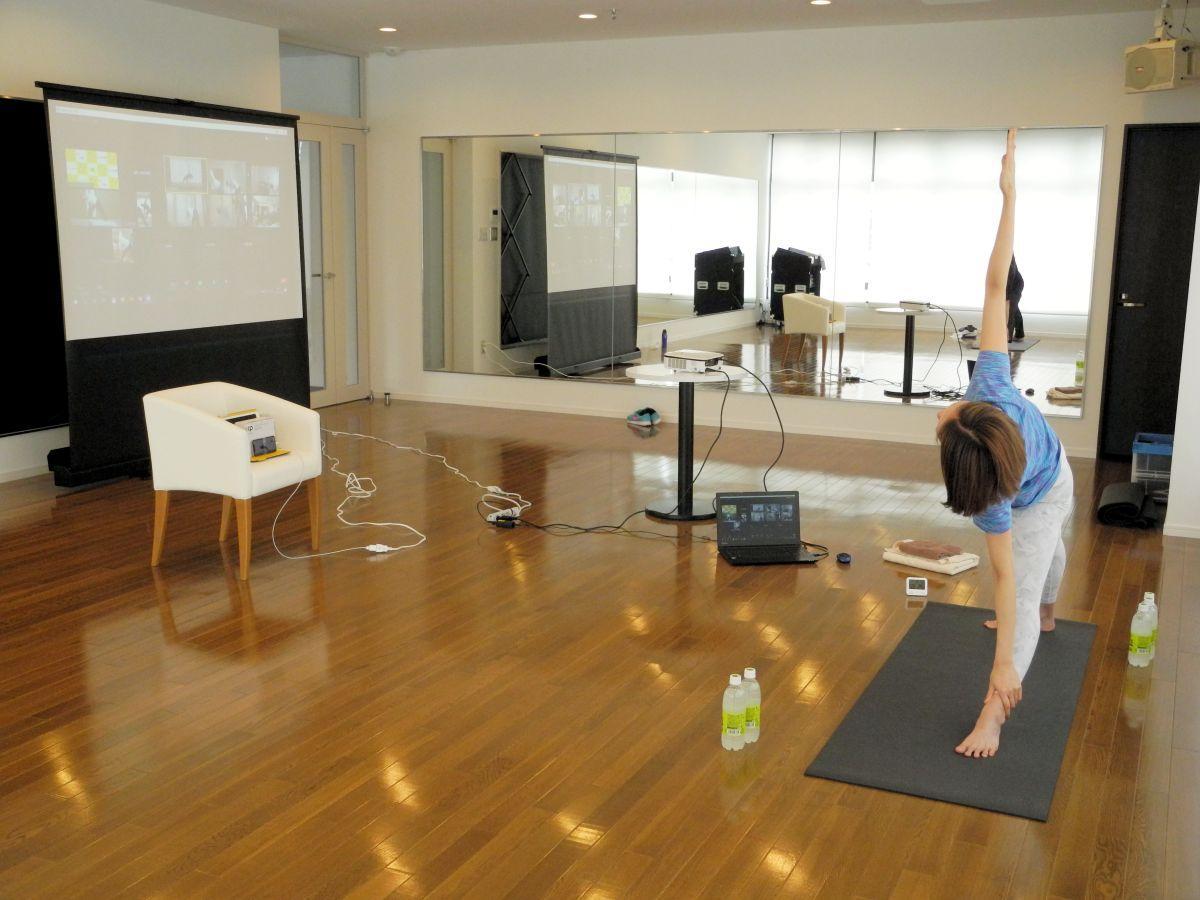「三角のポーズ」を指導する佐藤さん。オンラインでつながる参加者も同じように体を動かす