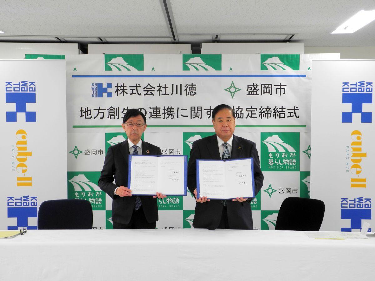 互いに署名した協定書を手にする谷藤市長(右)と川村社長(左)