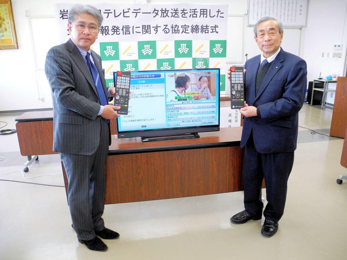 矢巾町の情報が表示されたテレビの前でPRする畠山社長(左)と高橋町長(右)
