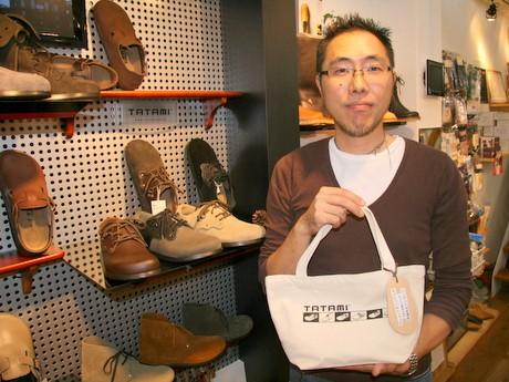 TATAMIの前でオリジナルトートバッグを手にする中村さん