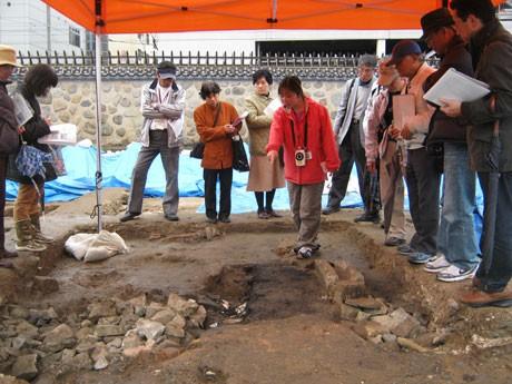 事前に開催された発掘現場の説明会に聞き入る「さるくガイド」ら