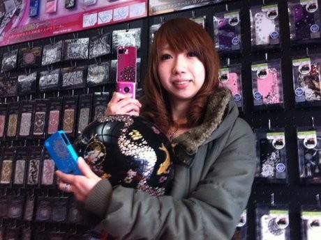高蒔絵装飾をした携帯やヘルメットを手に来店を呼びかける桑本知夏さん。