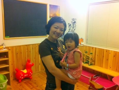 教室内で娘のひよりちゃんを抱く平朝子さん