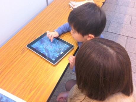 iPadで画像を楽しむ田賀農虎太郎(たがのこたろう)くんと母の有希さん