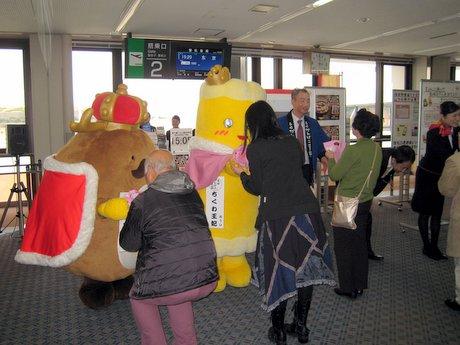 長崎空港の出発ロビーで長崎かんぼこ王国の「竜眼王」(左端)と「ちくわ王妃」から「長崎おでん」を手渡される当選者