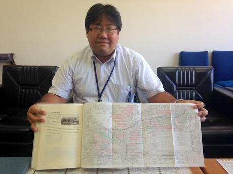 路線変遷図が閉じこまれた社史を紹介する松坂勲・経営企画室長