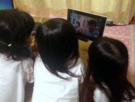 タブレット画面に映るモスクワのアレクセイさんにスカイプで呼び掛ける子どもたち