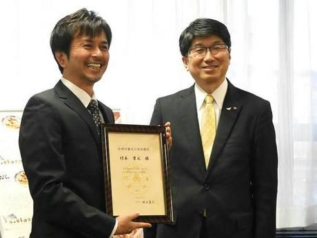 田上市長(右)から依頼状を受け取る竹本さん