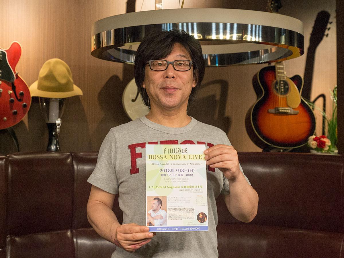ライブのチラシを手に持つ竹村さん