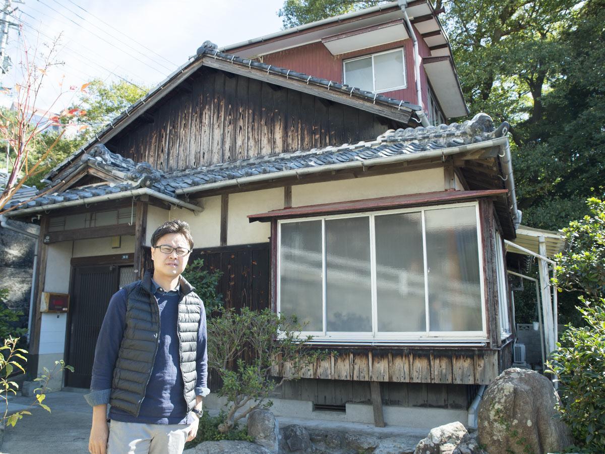 民泊施設の古民家前に立つ小笠原さん