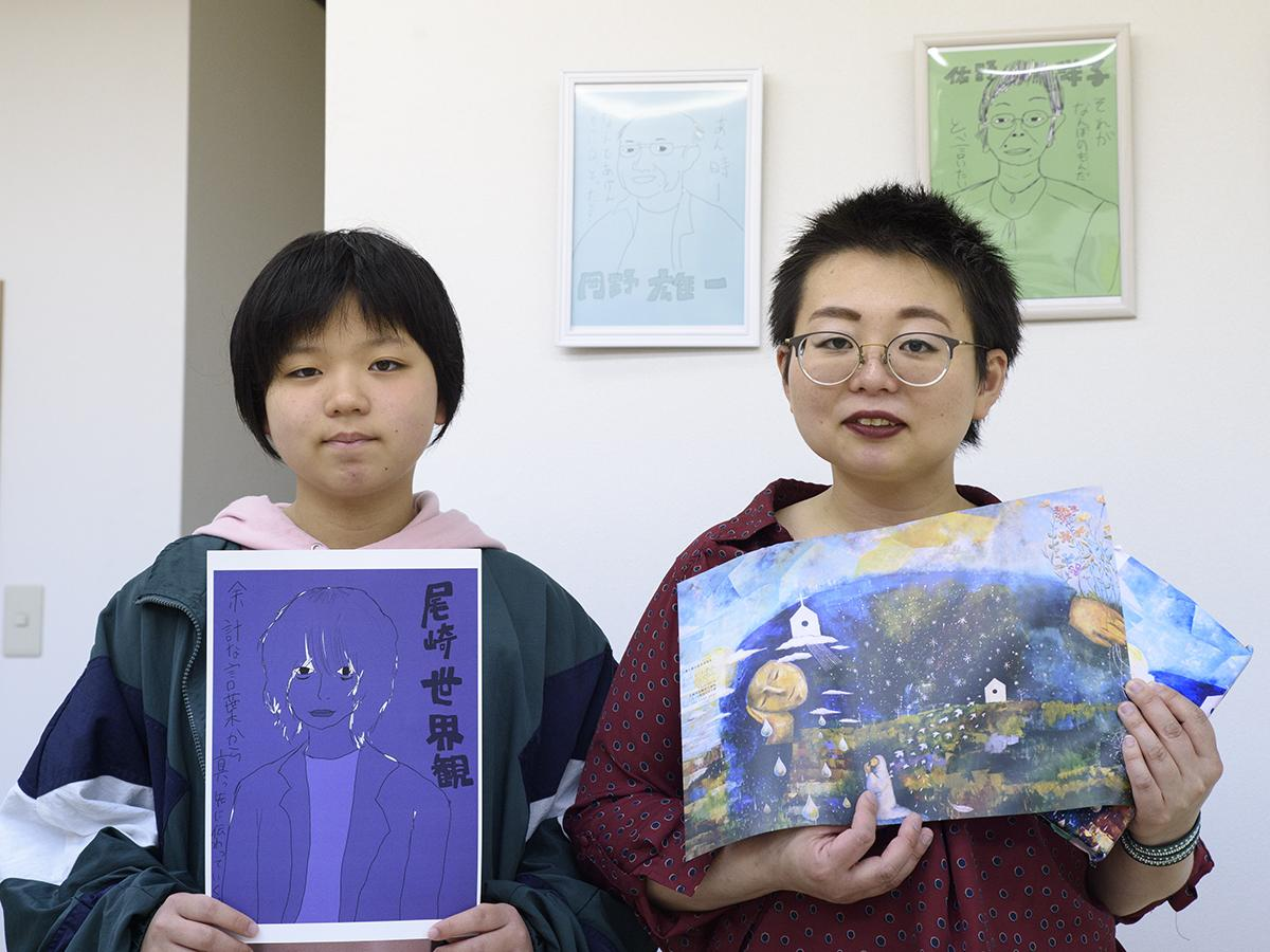 オリジナルのブックカバーを手にする店主の古屋さんと娘の幸香さん