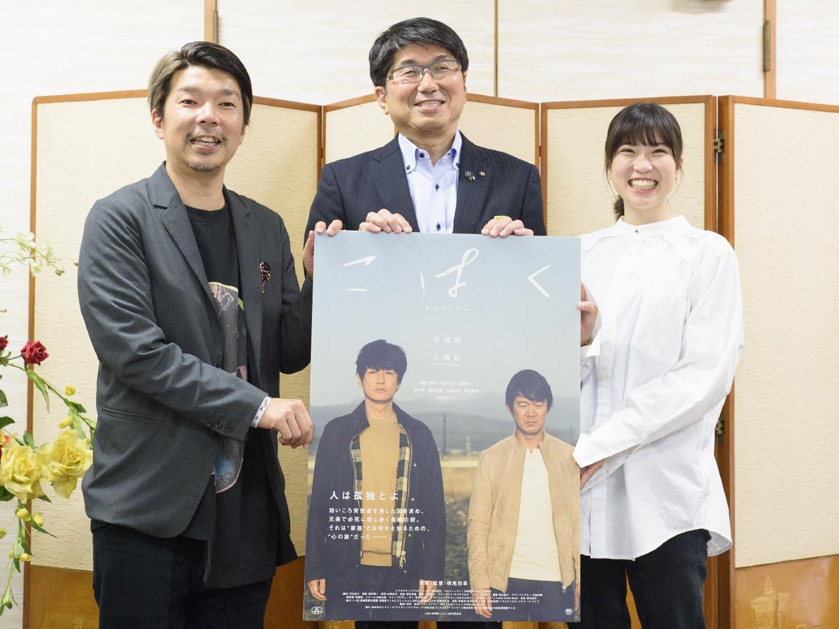 映画のパネルを手にする横尾監督(左から)田上市長、塩田さん