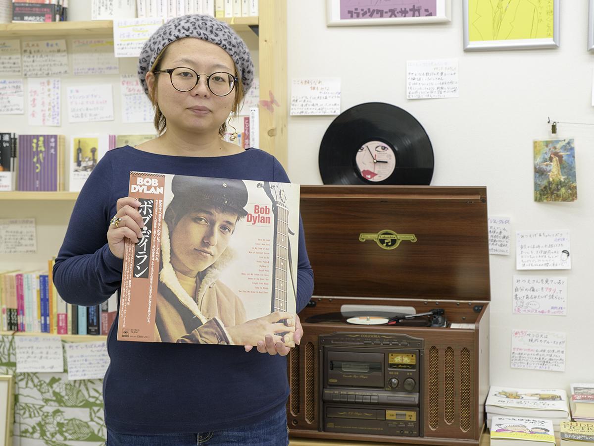 ボブ・ディランのレコードを手にイベントへの参加を呼び掛ける古屋桂子さん