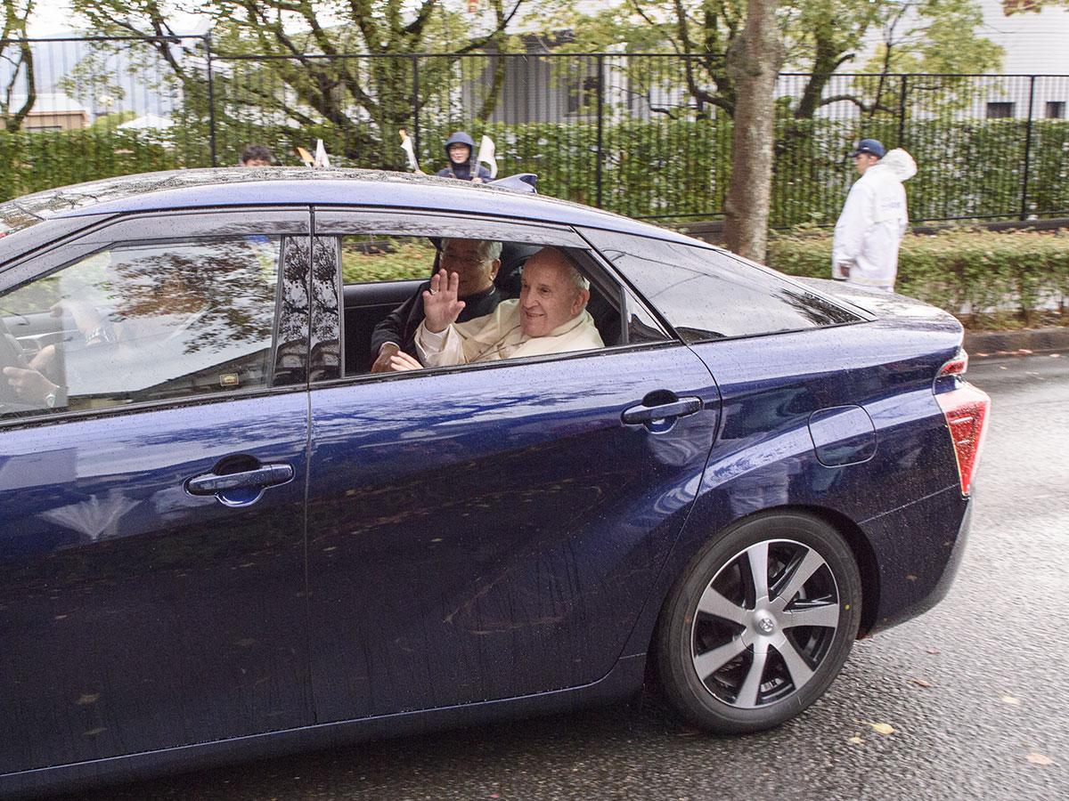 移動中の車から沿道の歓迎に笑顔で応えるフランシスコ教皇