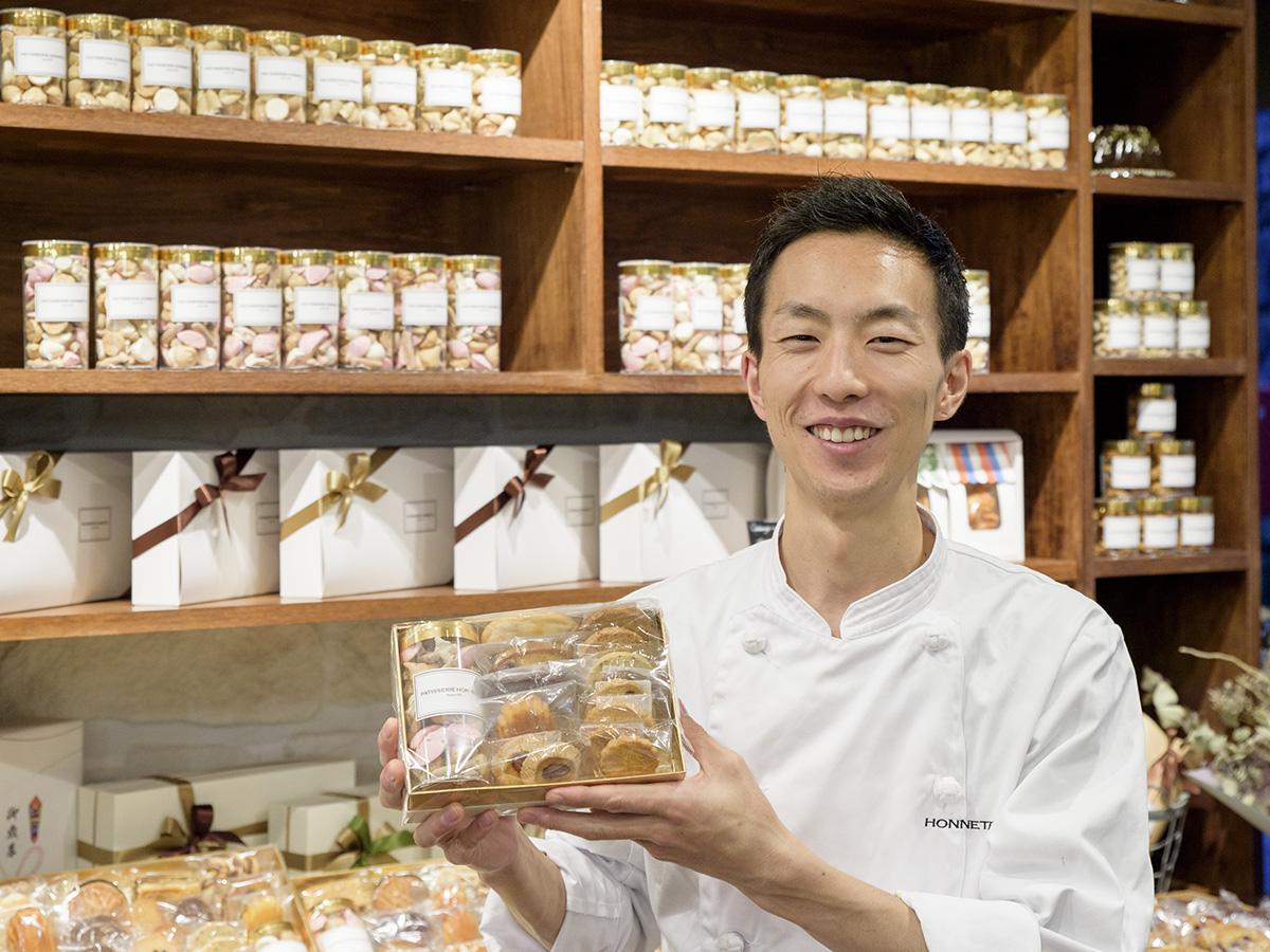 看板商品の焼き菓子を手に笑顔を見せるオーナーシェフの下野さん