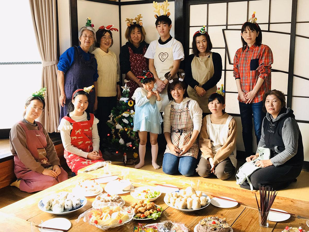 料理を囲んで記念撮影 上段左端が会長の高橋智子さん