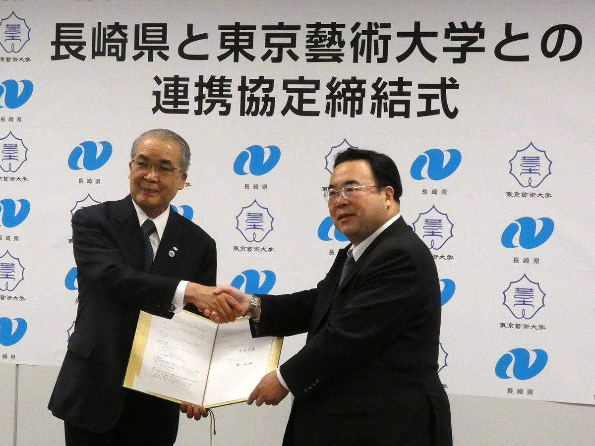 署名後に握手を交わす中村知事と澤学長