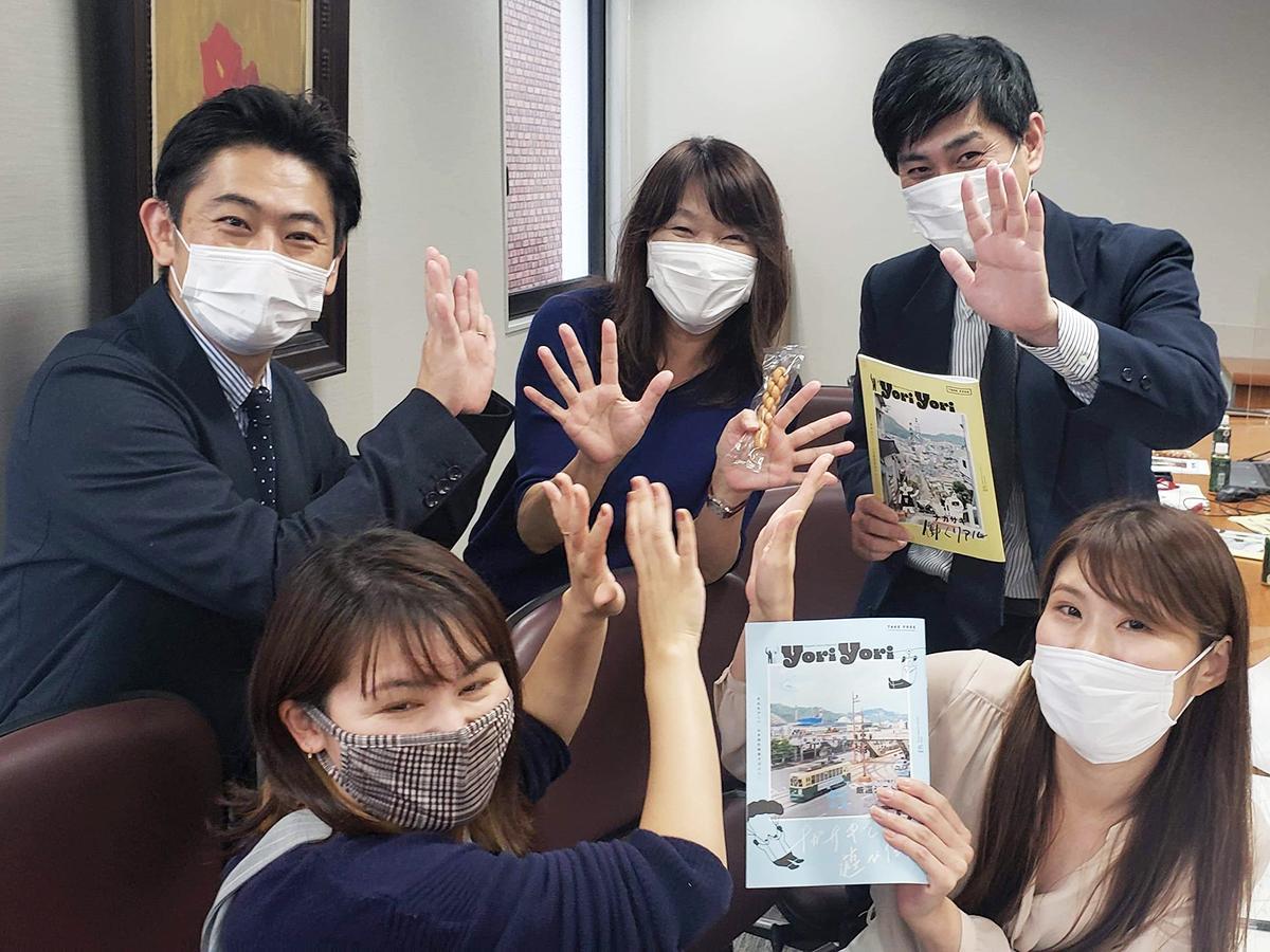 情報誌「yoriyori」と中華菓子「よりより」を手に意気込みを見せる原田さん(後方中央)ら市職員と長崎文化放送の編集スタッフ