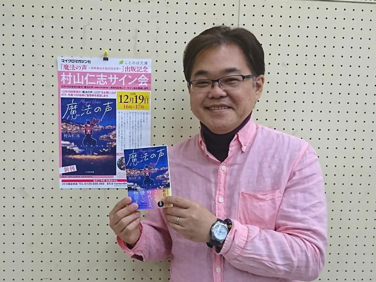新作小説「魔法の声」を手にPRする村山さん。