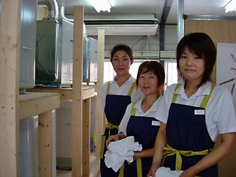 沖縄で初の洗濯代行サービスを手がける「モトエ」の川島マネージャー(左)とスタッフのみなさん