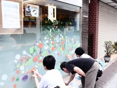 店舗の窓にクレヨンで絵を描くメンバーたち