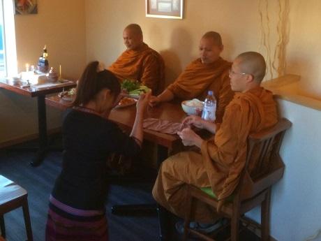 僧侶による開店前のお祈り後に食べ物を献上している様子