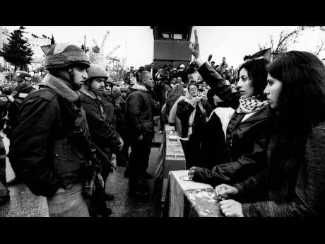デイズジャパン広河隆一代表2002年撮影の「エルサレムのアラム検問所でイスラエル軍に向かってVサインを掲げるパレスチナ人女性」